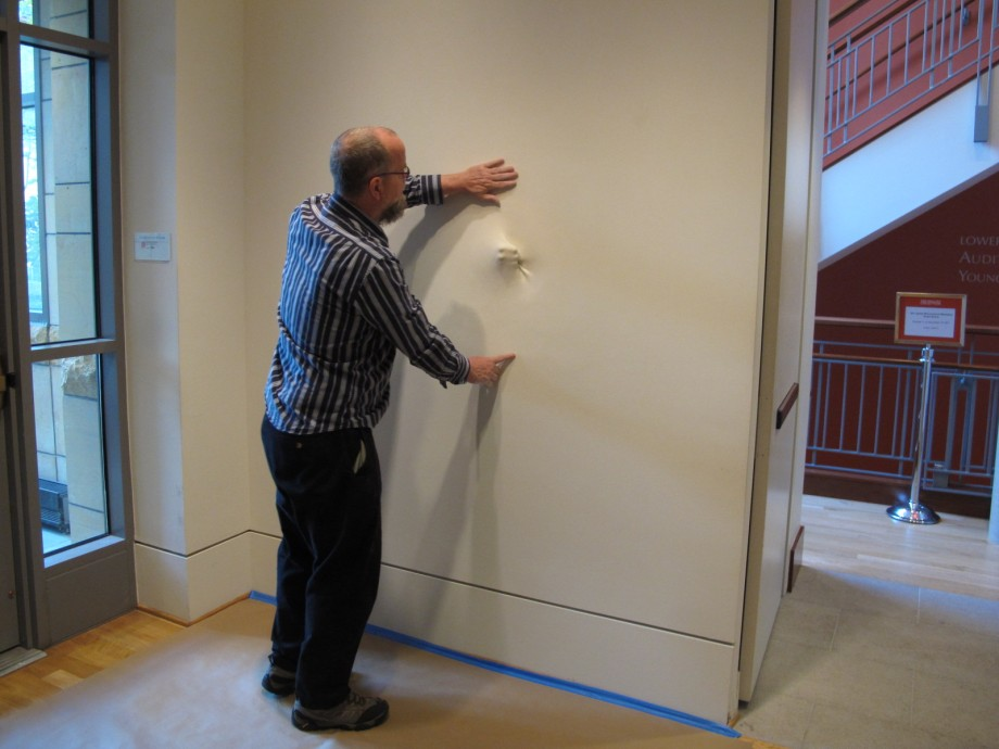 Preparator Bill Koberg examines the wall containing a portion of Bala's Sk(in) sculpture, preparing to de-install the work.
